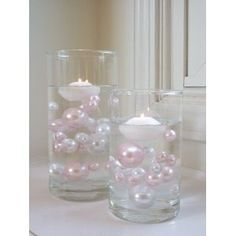 Pearls and candles floating in cylinder
