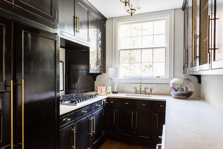 Small Black Contemporary U Shaped Kitchen Features Glossy Black Cabinets Accented With Brass Hardware An Black Kitchens Small U Shaped Kitchens Kitchen Remodel
