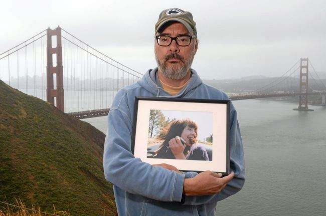 John Brooks holds a photo of his adopted daughter Casey in the Marin Headlands near Sausalito.