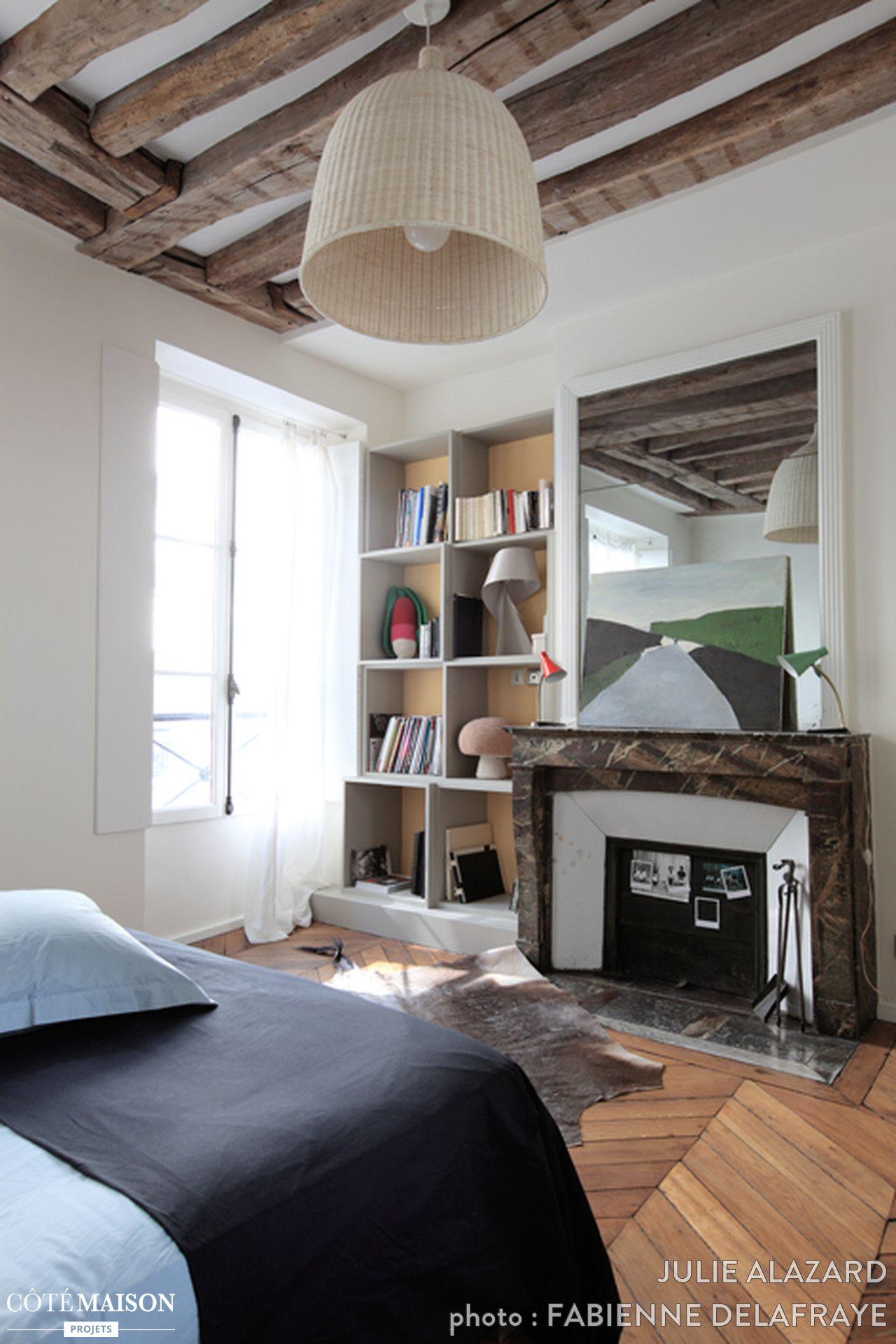 Une chambre avec une cheminée et du parquet. Au plafond, les ...