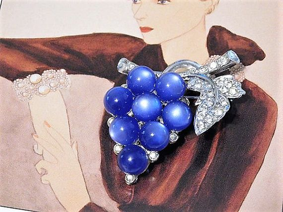 ITEM # 121656  Antique 1940s signed CORO moonglow lucite grapes and pave crystal rhinestone brooch. This brooch consists of 8 blue moonglow lucite beads to form the cluster of grapes with pave European cut crystals set in a rhodium plating.  Brooch measures 2 1/8 in length and 1 1/2 at its widest.  ****Dots on the lucite are from the camera and not on the lucite****  Condition: Very good antique condition with typical wear due to age and handling. Light surface scuffing on two beads...