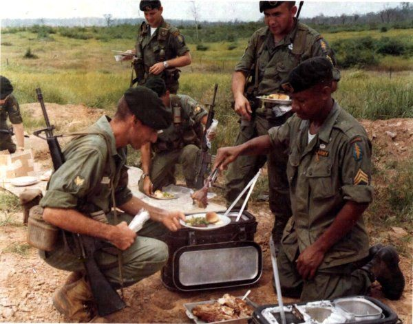 """Members of Det """"A"""", 5th Special Forces Group, located north of Saigon in War Zone D, are served their Thanksgiving Day dinner a little in advance of """"Turkey-Day"""". With two regiments of North Vietnamese Regulars in the vicinity, it is unlikely the men will have a quiet Thanksgiving Day. Prepared at a distant base, the complete hot meal was flown in by helicopter during a lull in the fighting."""