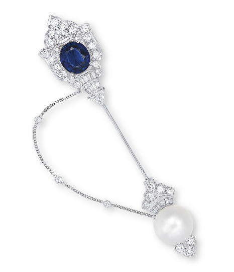 A SAPPHIRE, CULTURED PEARL AND DIAMOND JABOT PIN   The pierced diamond shield-shaped plaque, centering upon an oval-shaped sapphire, accented by baguette and triangular-shaped diamonds, to the detachable white cultured pearl terminal measuring 12.3 to 12.5 mm, embellished by brilliant and baguette-cut diamonds, joined by a fine chain enhanced by collet-set diamond details, mounted in 18k white gold, 8.5 cm long. Art Deco or Art Deco style