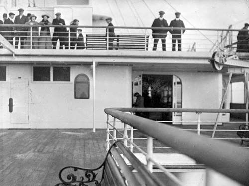 Taken from the aft end of A-deck, this photograph is looking for it toward the rear of the ships superstructure. On the deck abode, a group of second-class passengers stare back at the camera.