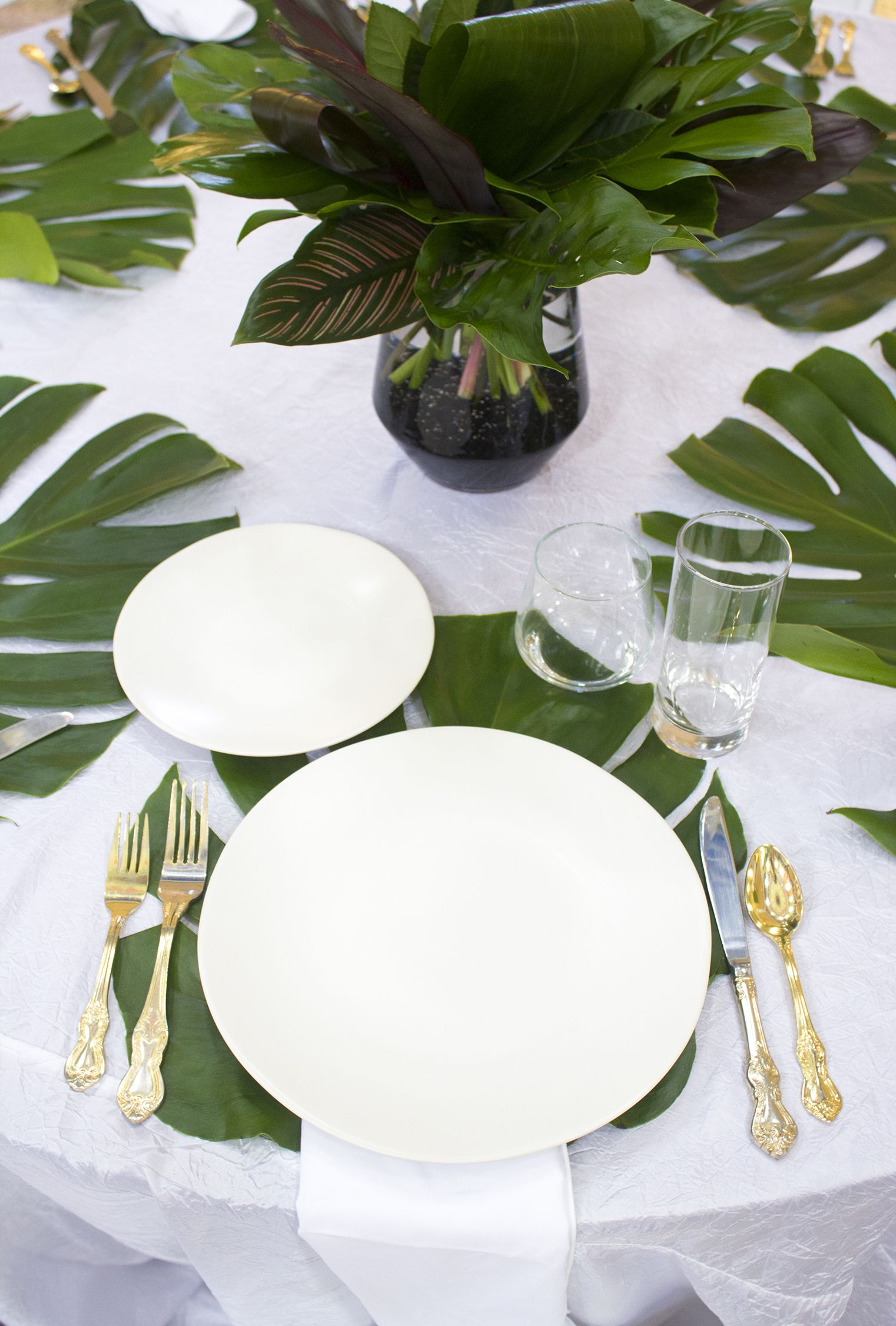 Fresh And Vibrant Place Setting With An All Greenery Centerpiece And Real Monstera Leaf Place Mats Provided Greenery Centerpiece Wedding Leaves Place Settings