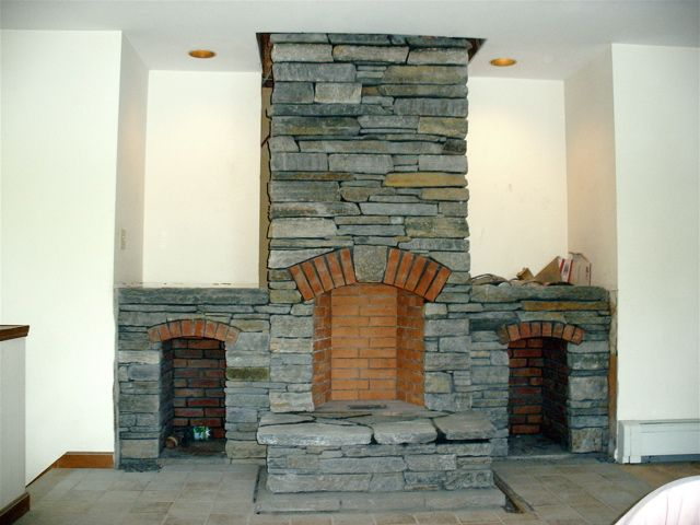 A stone chimney, with raised hearth and two side wood boxes.  We replaced an old damaged fireplace that was built maybe in the 80's.  The homeowners asked that we stick to the same design.  We did change the stone and built it much tighter and safer the it's predecessor.