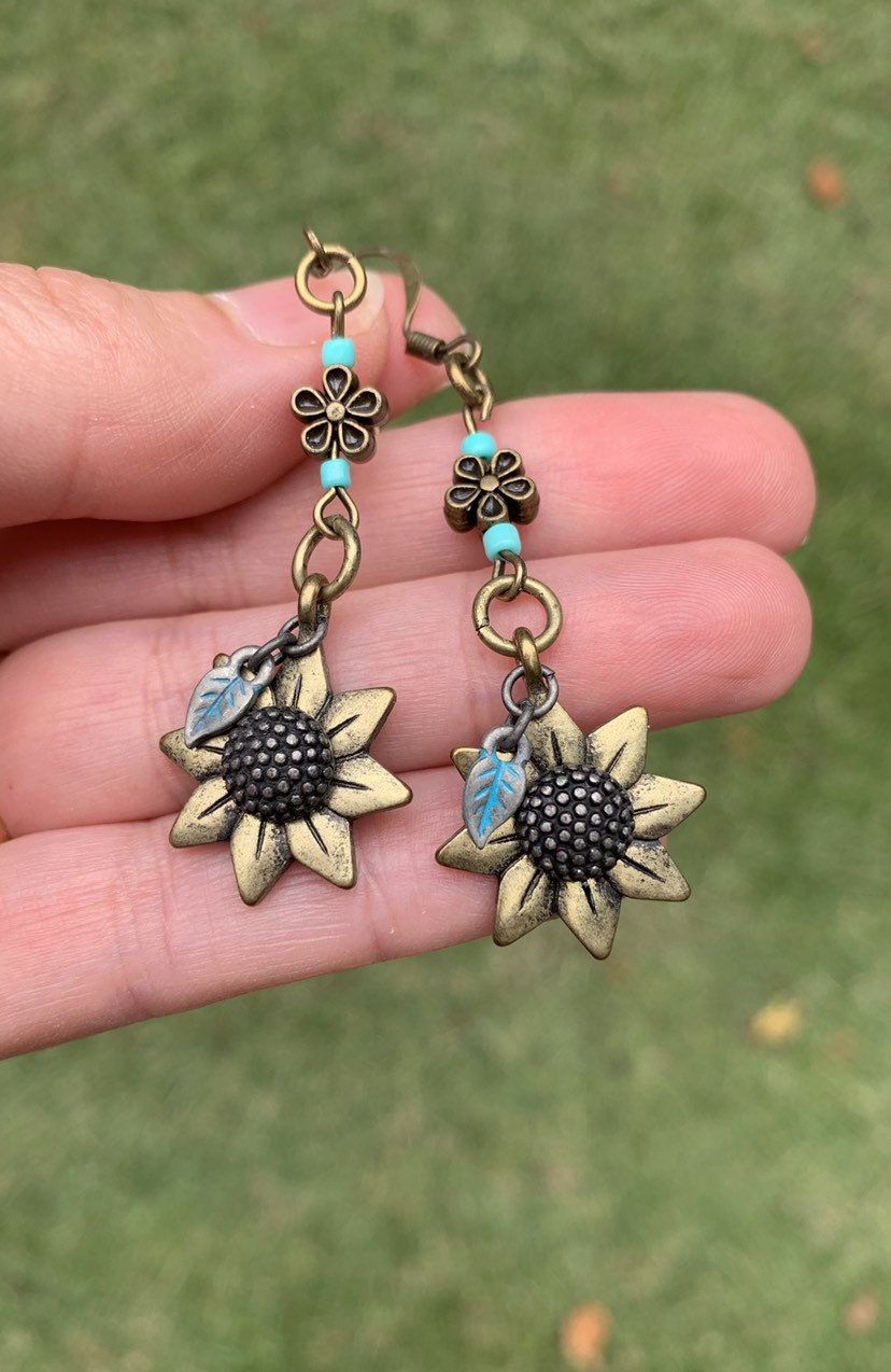 Patina Sunflower Charm Earrings  Bronze Floral Earrings  Rustic Jewelry is part of Etsy jewelry earrings, Rustic jewelry, Handmade jewelry, Etsy jewelry, Jewelry gifts, Handcrafted jewelry - 4 inches  📌Antique bronze sickle ear wires 📌Clear rubber security backs  Be sure to look at the Announcement section of my boutique where you will find information on sales and special discounts! KayBejeweled etsy com