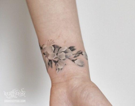Tatouage fleur de cerisier élégant blanc et gris sur le poignet par  Graffitoo