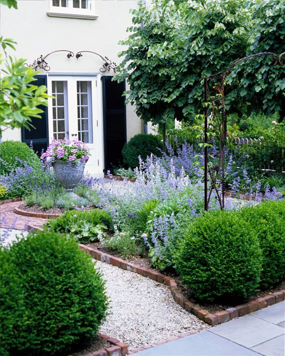 Courtyard with gravel paths and beds edged in brick - really like the gravel, but maybe too casual to use in courtyard/patio area? Like the boxwoods. Also like the flowers, but they would not always be blooming Love using the pea gravel!!