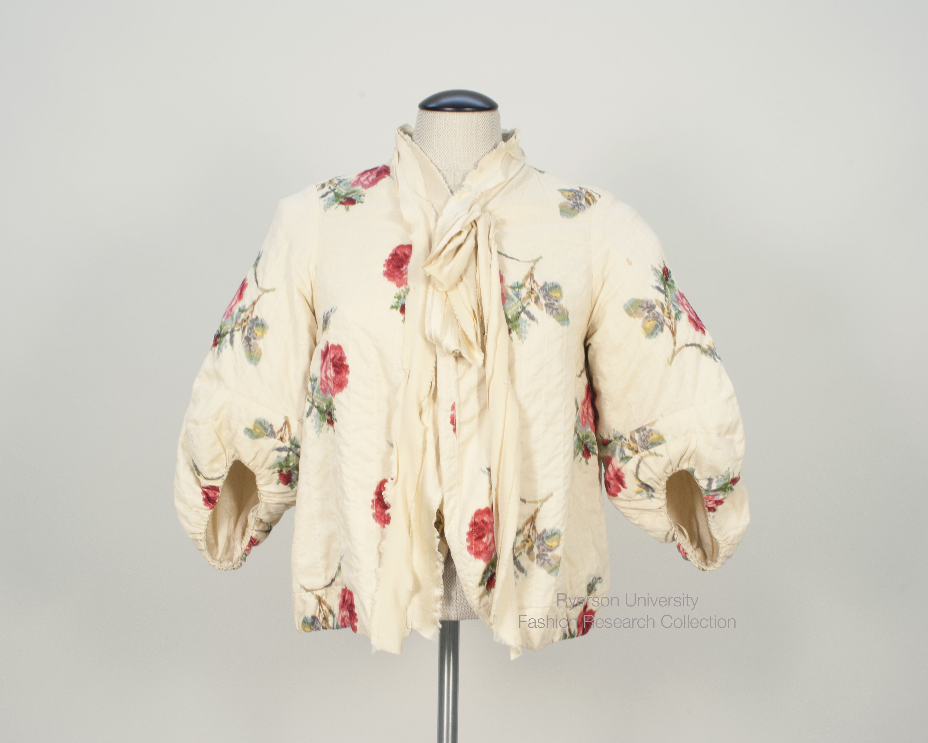 Tea-stained beige cotton with printed red rose 'bed-jacket' with 3/4 balloon sleeves. Textile is top stiched in wide vertical rows. Frayed beige silk ties at neck with set bow  on R side. Lined in beige silk with drawstring at middle back of lining. Size 6. By Mercy of Toronto, Ontario. C. 2008. FRC 2015.06.001