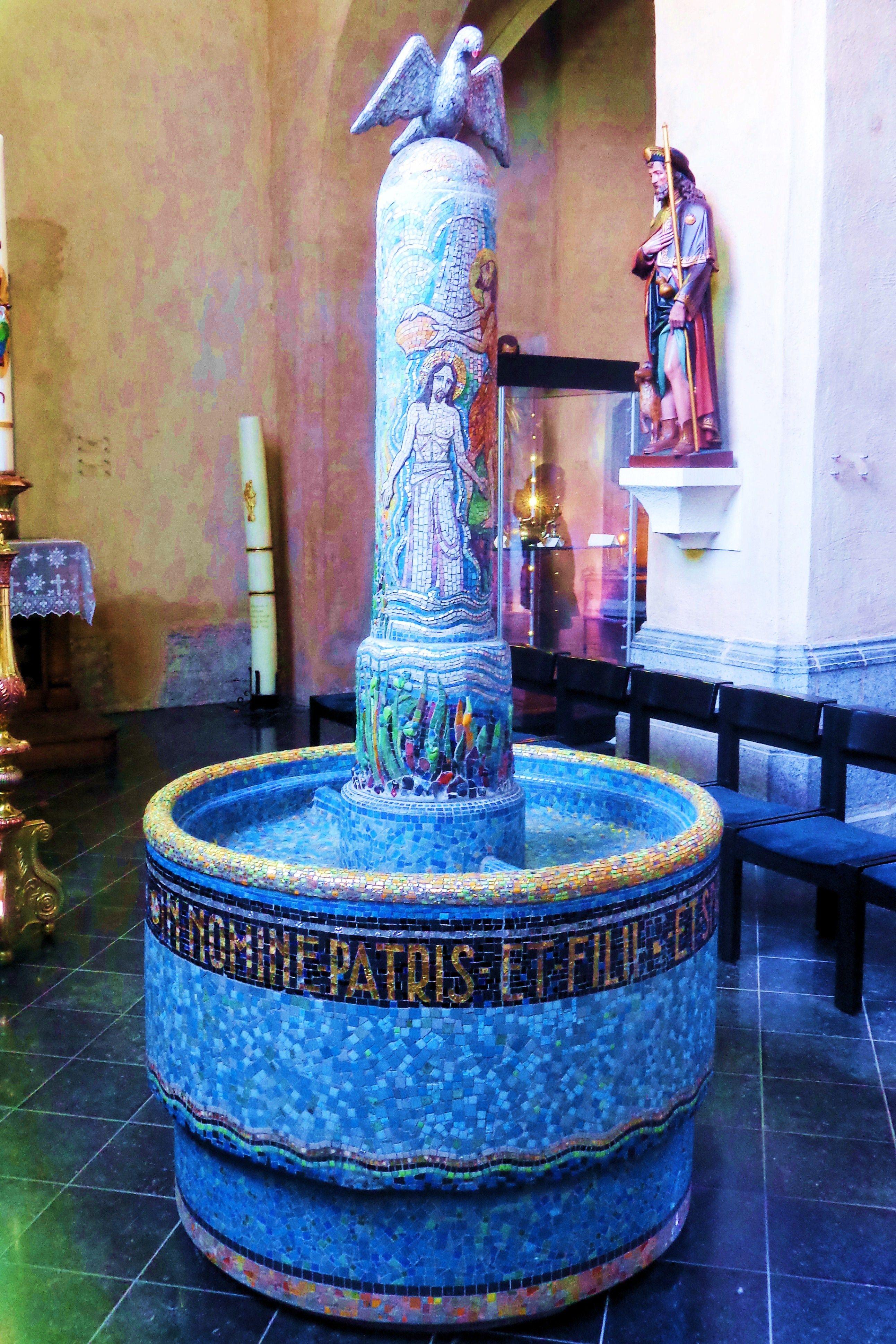 Deze doopvont werd in 1941 door Antoon Molenboer gemaakt van Venetiaanse mozaïeksteentjes. De doopvont was oorspronkelijk bedoeld voor de Heilige Geestkerk in Parijs, maar deze kerk werd in de loop van de Tweede Wereldoorlog verwoest. Op de kolom de Heilige Geest als duif en een afbeelding van de doop van Christus door Johannes de Doper.