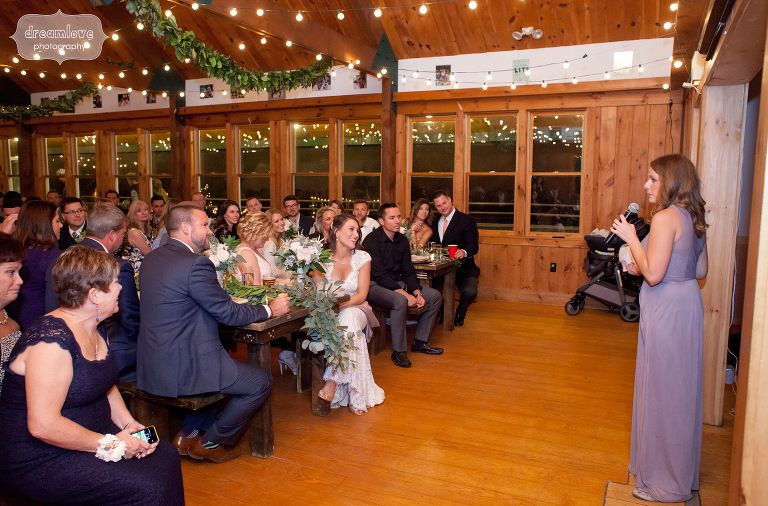 Windsor Mountain Camp Wedding reception barn set up with family style dinner tables and eucalyptus table runners!