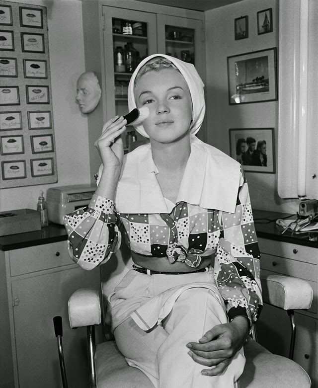 1948: Marilyn preps her skin with a skin brush before applying makeup.