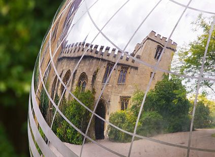 Balliol College, Oxford, reflected off the mirror polished stainless steel globe of a Moon Dial