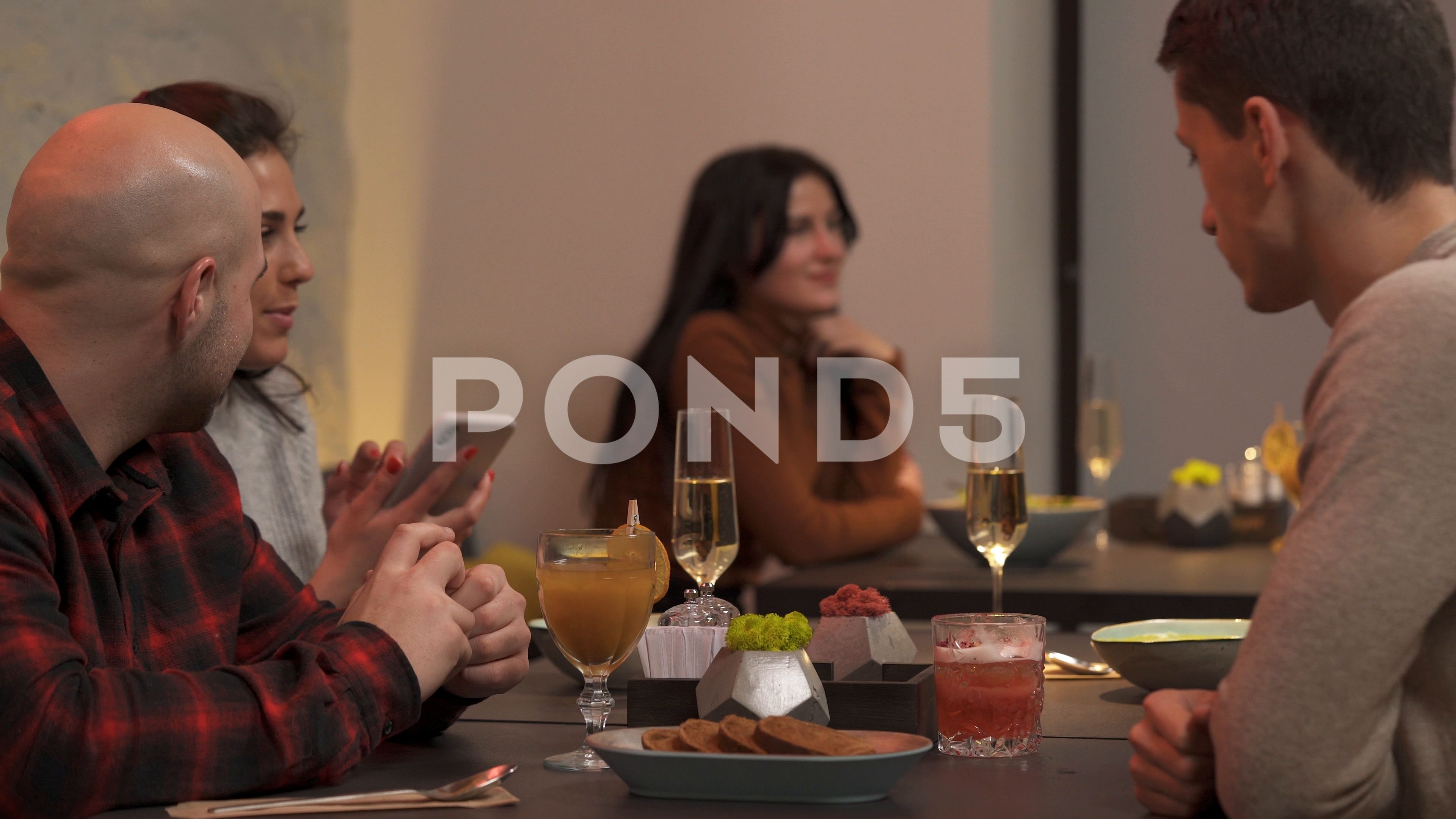 A closeup view of a young people having dinner at a bar with friends Stock Footage youngpeoplecloseview