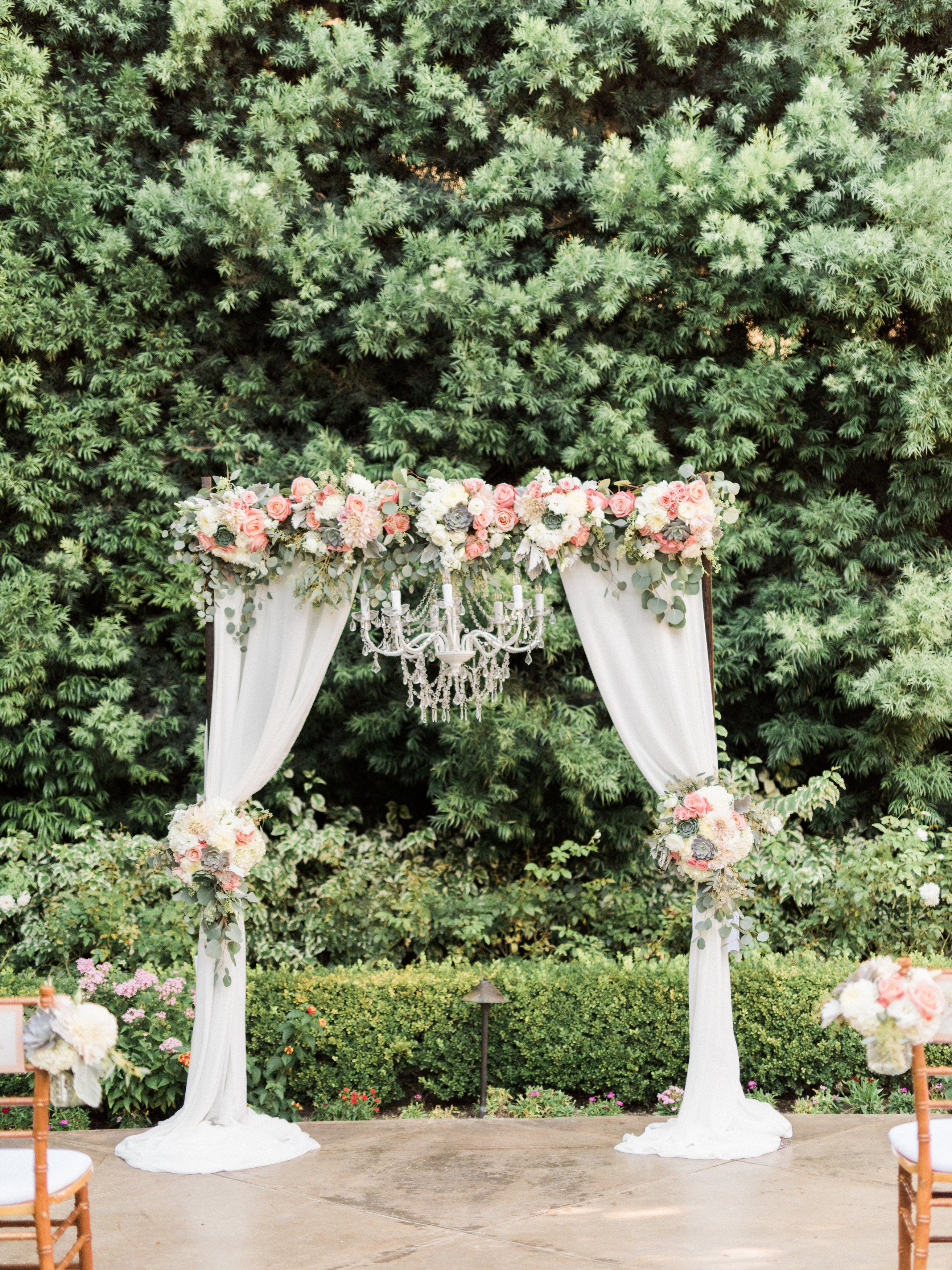 Wedding ceremony arch with draping fabric and chandelier Succulents