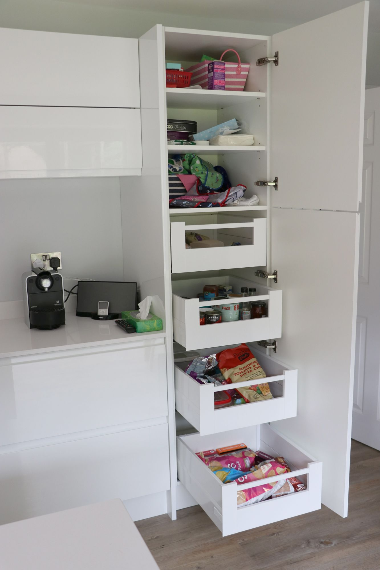 Modern white handleless kitchen with dynamic larder unit