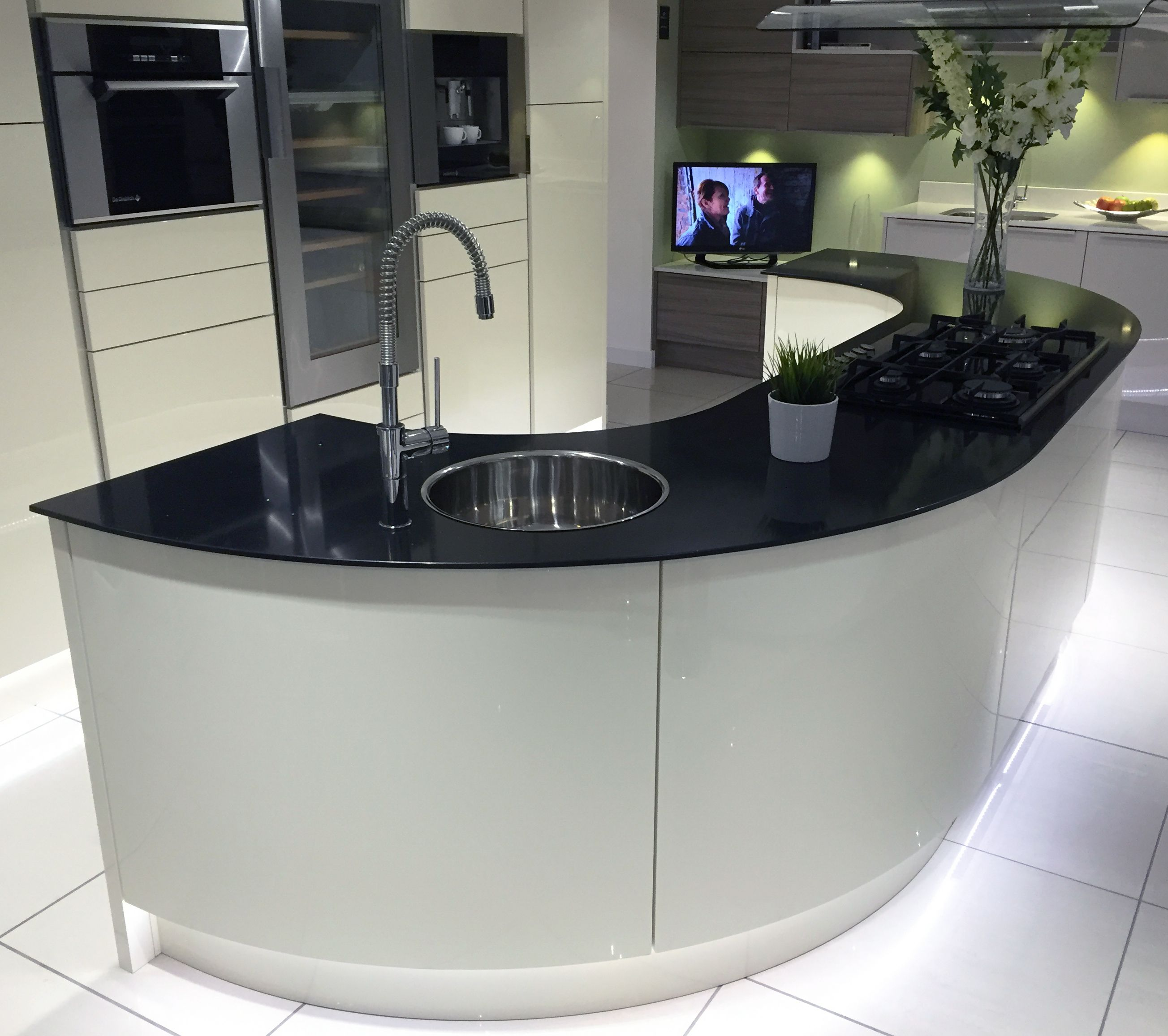 Gloss Ivory kitchen island with large curved units and black glass