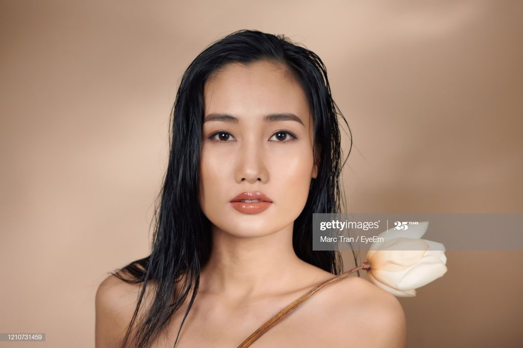 Closeup Portrait Of Beautiful Woman Holding Flower Standing Against Beige Backgr #Ad, , #Ad, #Beautiful, #Woman, #Closeup, #Portrait