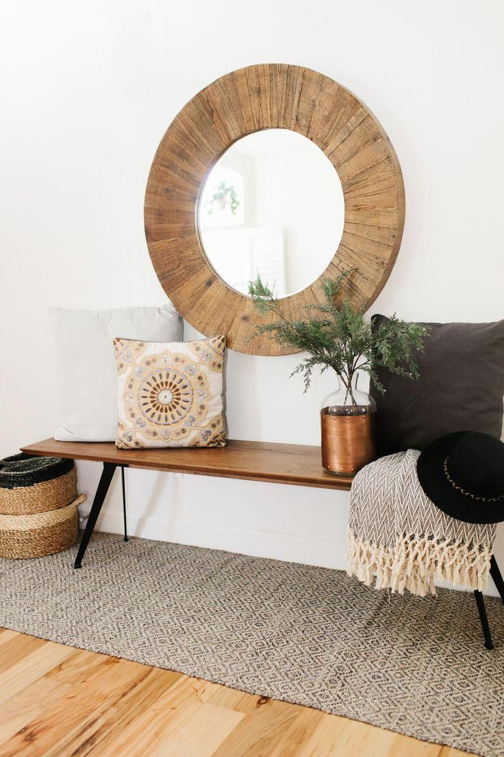 oversize round wood mirror with a midcentury modern style bench and cozy pillows and throws to add warmth #homedecor