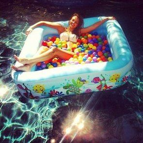 Pick up a blowup pool at the end of summer and fill with balls, with the end of season sales this is so much cheaper then buying a ball pit