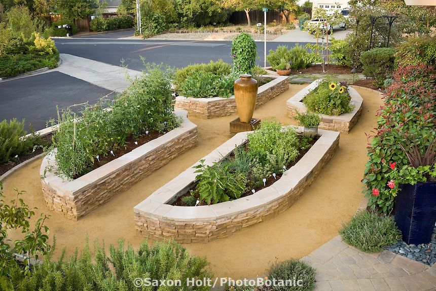 Stone raised bed vegetable beds in California front yard