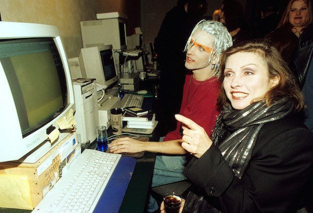 Photo of Debbie Harry from Blondie and a cyber goth share a computer and look at blank webpage togethe…