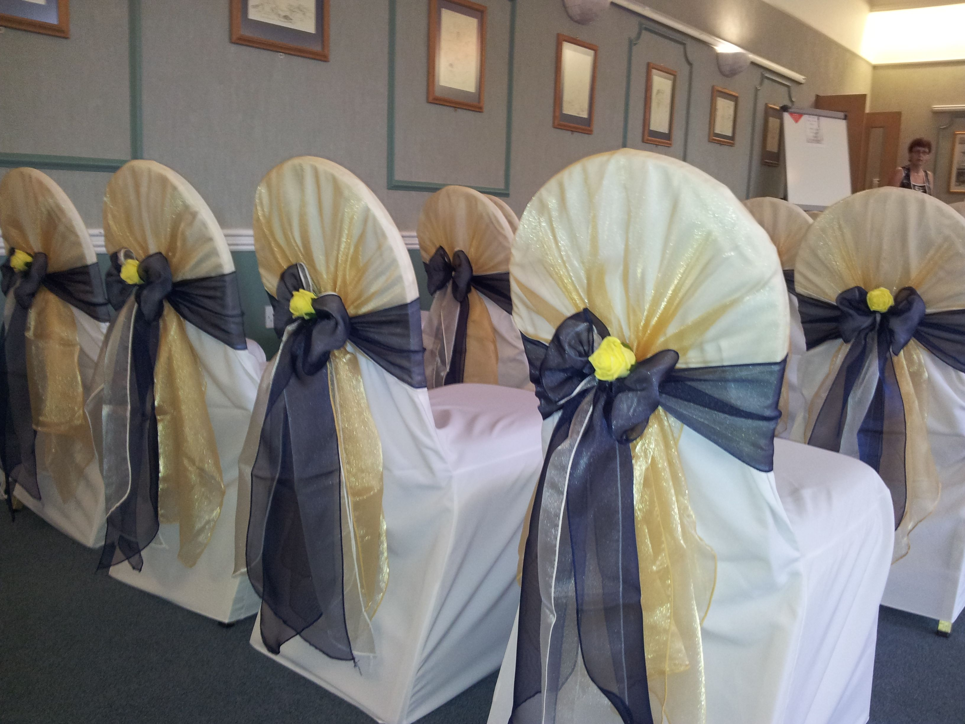 Gold Organza Shawl And Navy Satin Bows On White Chair Covers