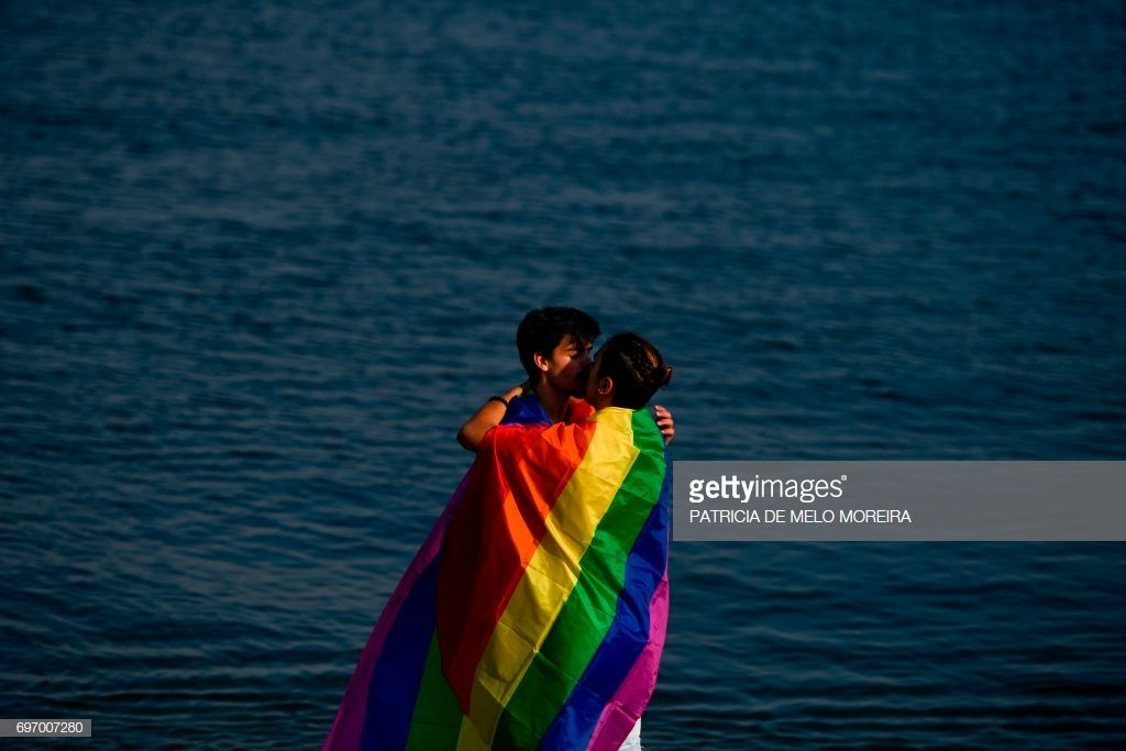 A Couple Wrapped In A Rainbow Flag Kiss Eachother In Front Of Tagus