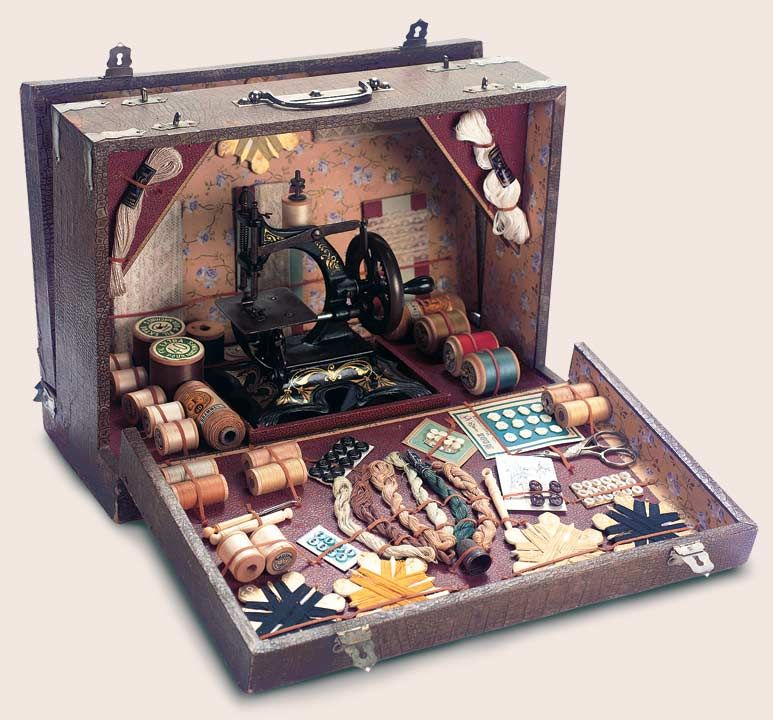 """Theriault's Antique Doll Auctions - French Sewing Menage - A wooden-framed case with paper covers and silver-plate handle and clasps,is designed to open at either side,to reveal an elaborately fitted interior. Posed in the center is a toy cast-iron sewing machine with original stenciled designs,and surrounding this are a number of sewing supplies and tools. The case is labeled """"La Petite Couturiere"""" on both sides. Excellent condition. French,circa 1900."""