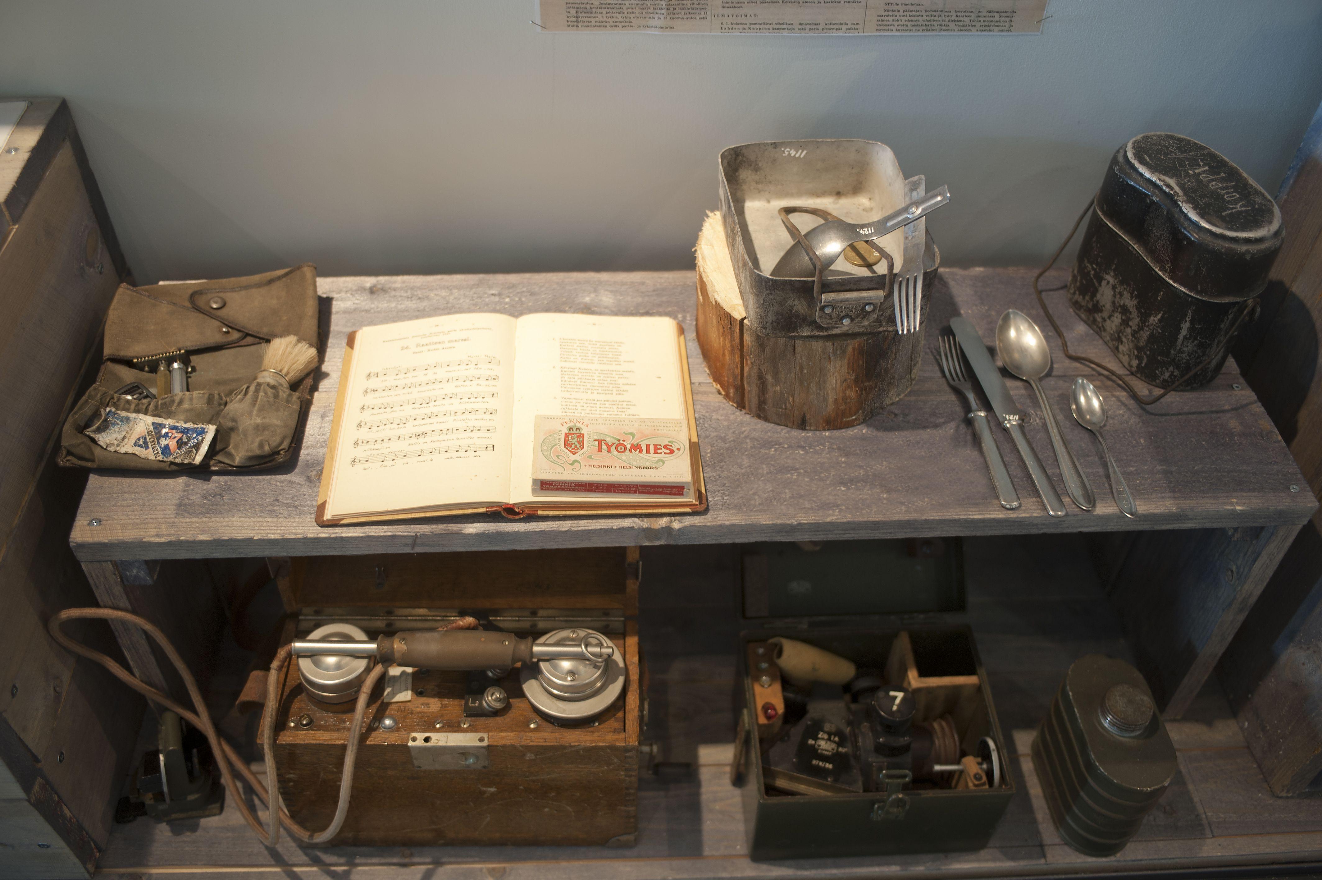 Suomalaisten sotilaitten ruokailuvälineitä, laulukirja, kenttäpuhelimia.
