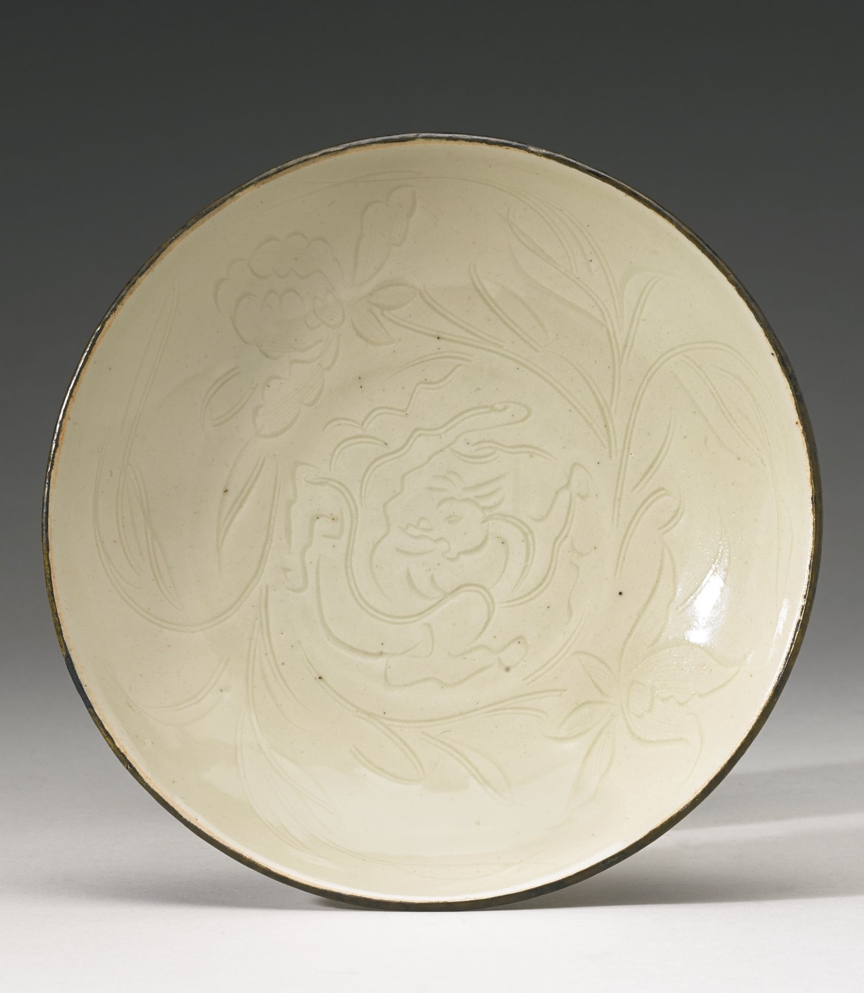 Lot 104  Sotheby's.  A RARE 'DING' DISH SONG DYNASTY of shallow saucer shape resting on a low wedge-shaped foot ring, the interior crisply carved with a chilong curled to form a medallion encircled by floral sprays, one bearing a large peony, the other a lotus, the petals with delicately incised and combed details, the underside plain, all under an ivory glaze, the rim bound in metal Diameter 5 5/8  in., 14.3 cm