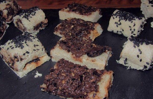 Cuisine monochrome noire, canapés à la tapenade, roulés au sésame noir