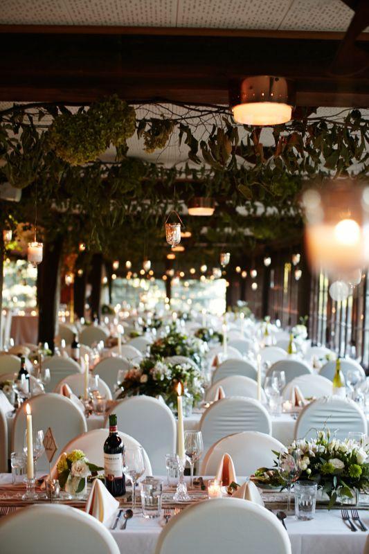 Greenery Garlands And Hanging Lanterns Decorate Wood Beam Ceilings