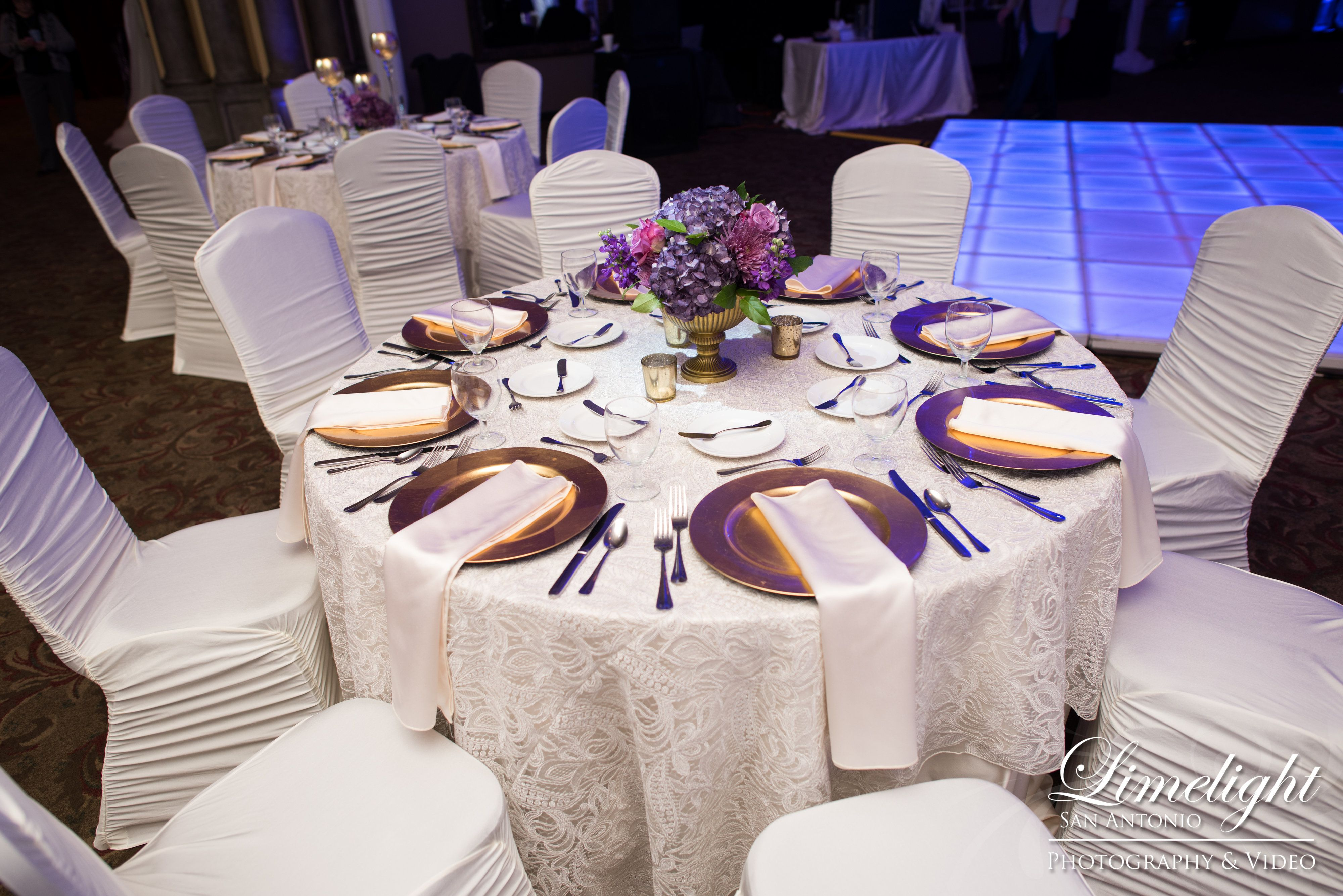 Guest Table Designed By Events By Reese With White Spandex Chair Covers Lace Linens With Gold And Purple Centerpieces Catering Wedding Reception Decorations