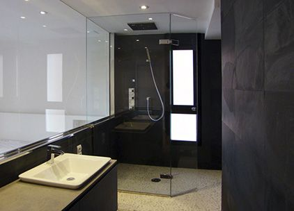 Foto de reforma de baño moderno en tono blanco y negro, lavabo sobre mueble y ducha con piedras blancas y pizarra natural negra y mampara cristal. #cuadroTRES #lavabo #blockSYSTEM #TRESGriferia #spain