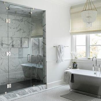 white beaded chandelier over modern cast iron bathtub