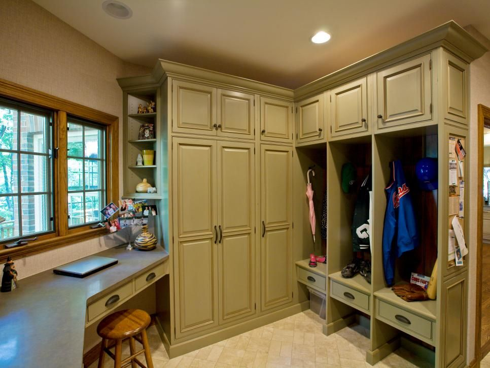 Olive Green Cabinetry In This Mudroom Boasts Ample Storage For A Busy Family