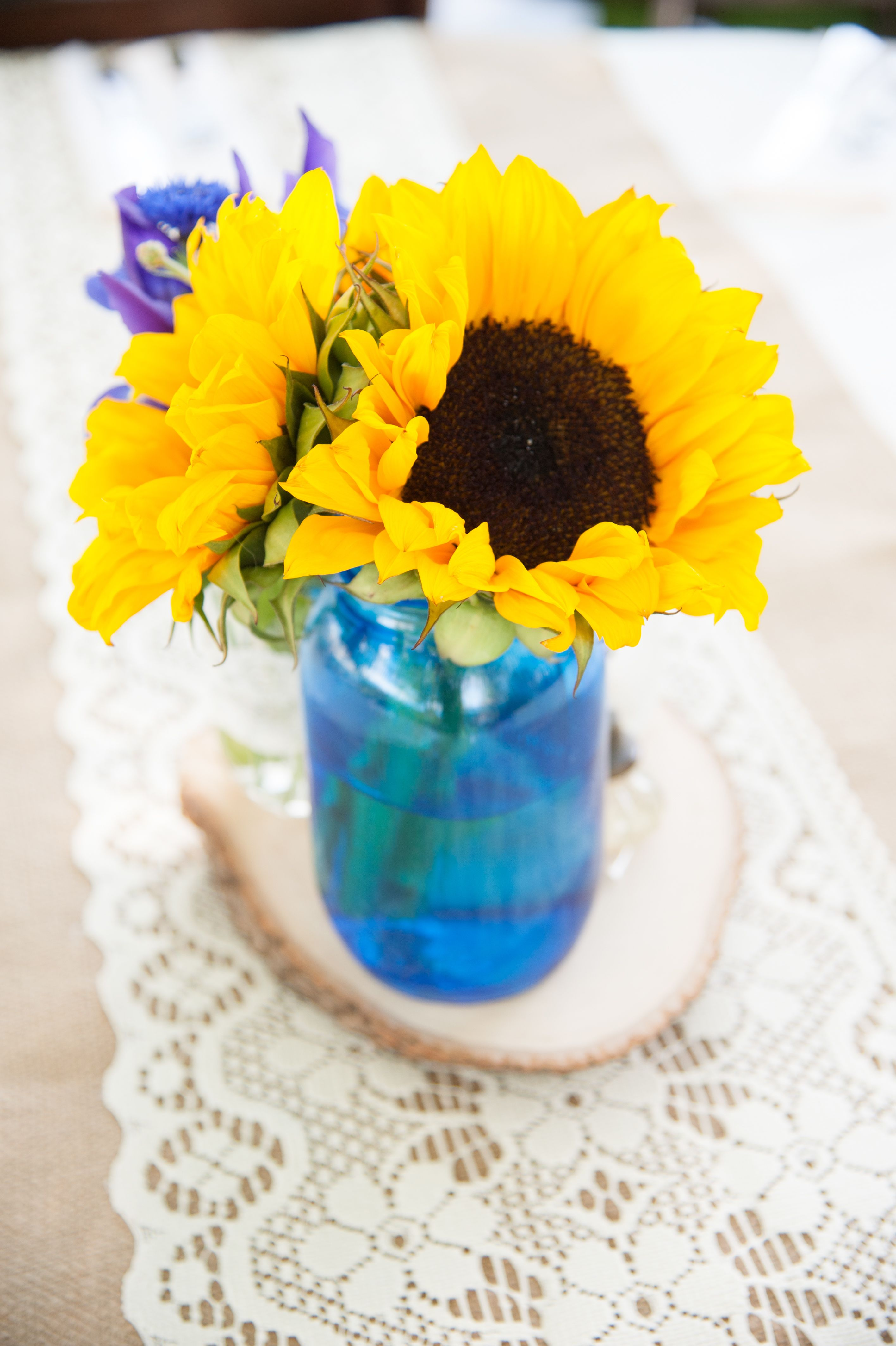 Lace runner for a rustic look with blue mason jar centerpieces on a