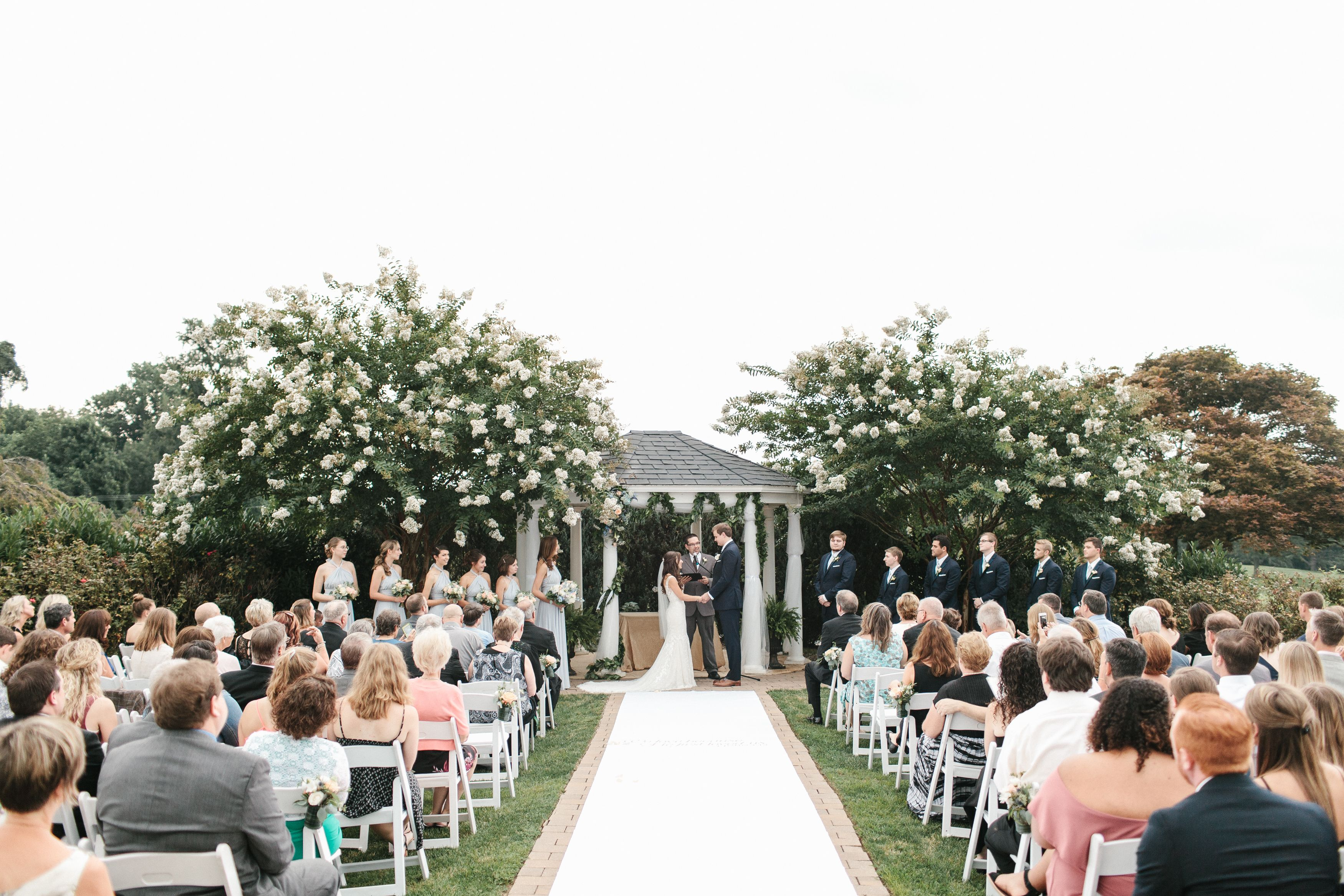 Outdoor ceremony in july walking down the aisle by penn oaks golf