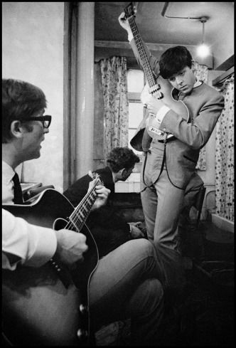 Philip Jones Griffiths—Magnum  John Lennon and Paul McCartney with guitars. England, Paul is tuning his bass, demonstrating why it pays to be tall if you play bass.