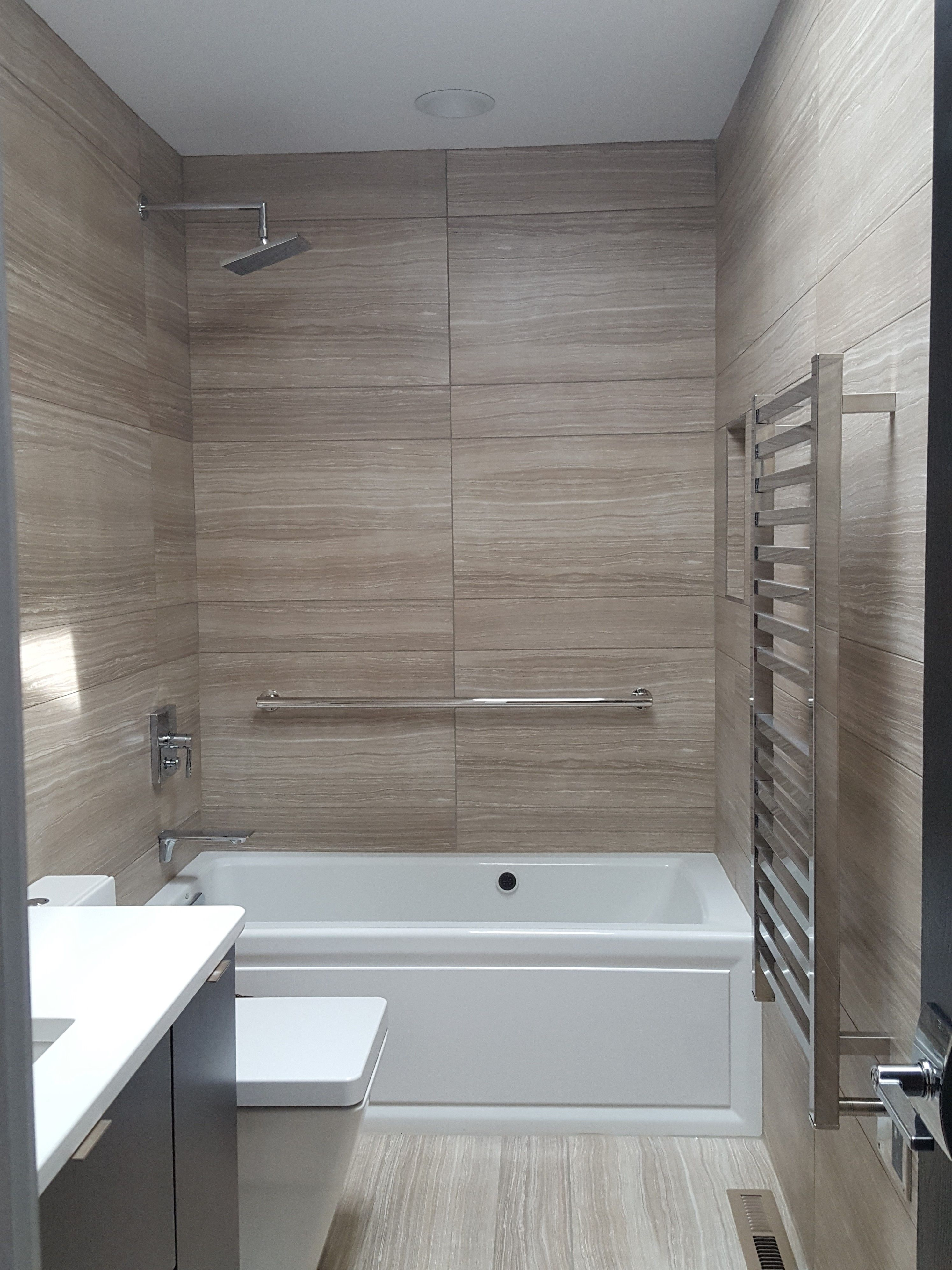 Large striated tiles, heated towel bar, recessed shampoo niche ...