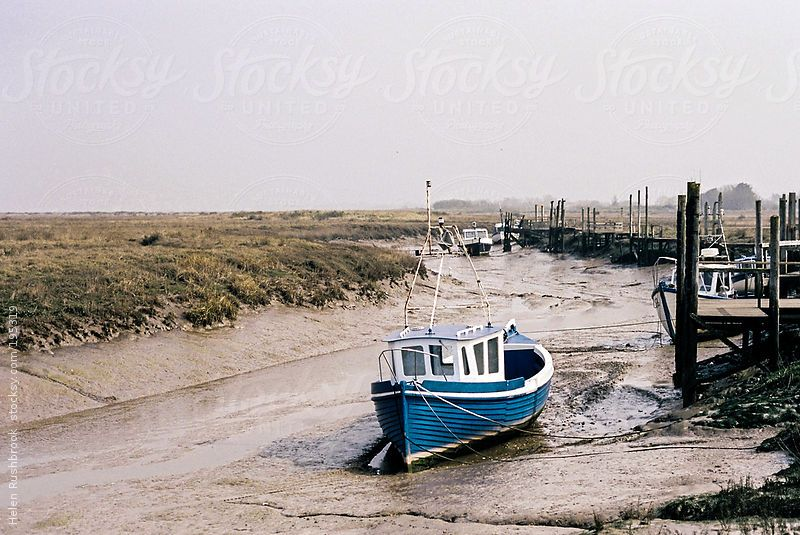 An old fishing boat moored in Alnmouth estuary at low tide
