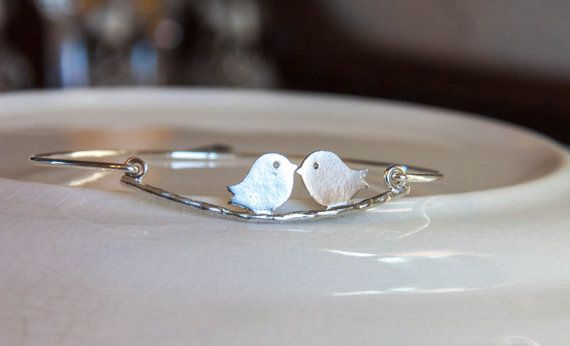 Two silver plated brass love birds with a sterling silver filled band. Each bangle is hand formed and then hand-hammered using a bracelet…