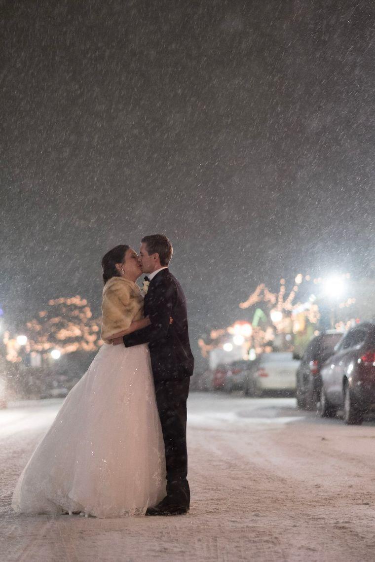 Bride kissing groom in the snow