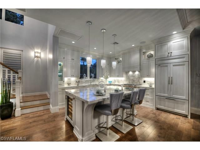 Gorgeous gray kitchen with center island seating and pendant lighting.  Olde Naples luxury beach estate - 9th Street South