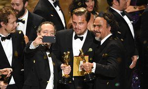 Cinematographer Emmanuel Lubezki, actor Leonardo DiCaprio and director Alejandro Gonzalez Inarritu, all winners for The Revenant take a selfie onstage
