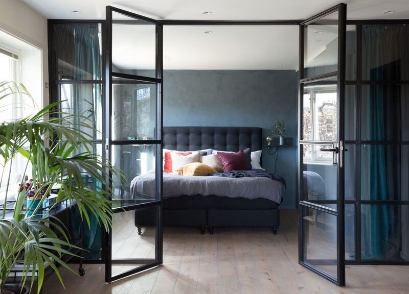 Glasswall with french doors dividing bedroom and living room…