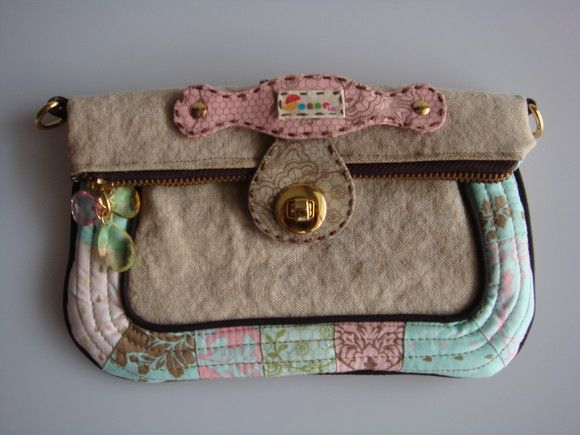 Esta bolsa possui uma alça removível e pode se transformar em carteira, bolsa de ombro e transversal. Ela é feita de lona estonada e detalhe em patchwork . R$70,00