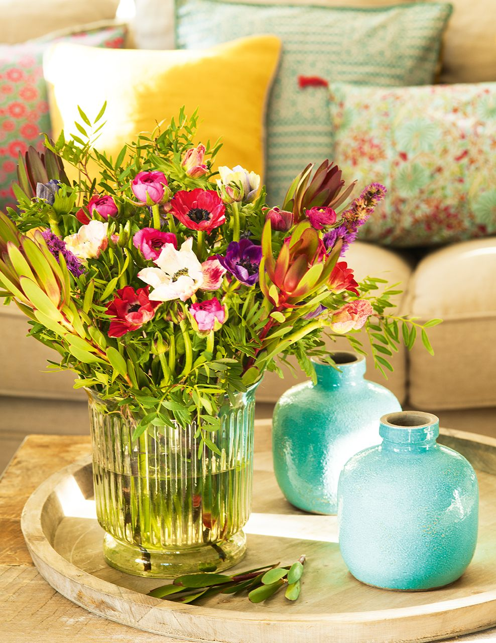 bandeja de madera con jarrones azules y jarrn de cristal con flores de colores
